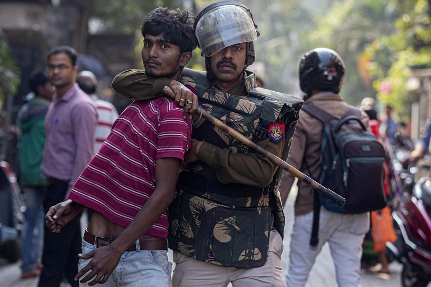 A policeman restraining a demonstrator protesting against the Citizenship Amendment Bill in India. Violent protests have broken in north-eastern India against naturalisation of illegal immigrants of any faith. PHOTO: ASSOCIATED PRESS