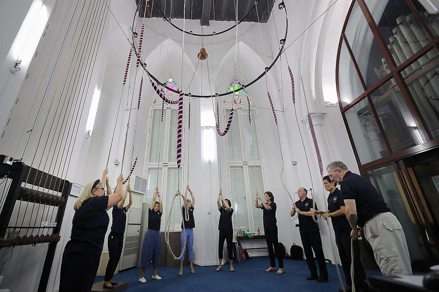 One of the team's trainers David Smith (at right) and tower captain Benjamin Tai (beside him) among bell ringers at St Andrew's Cathedral yanking on ropes attached to a custom-made structure that holds the bells, swinging them rhythmically through a