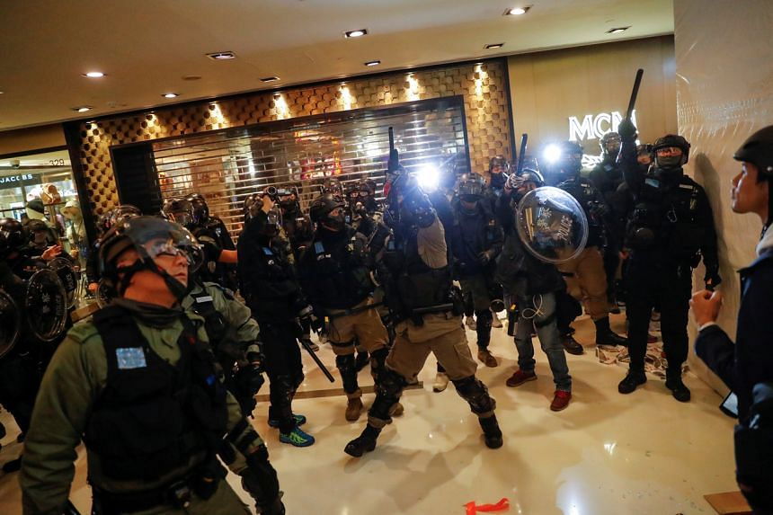 Police officers aim their weapons during a demonstration inside a mall in Hong Kong on Dec 15, 2019.