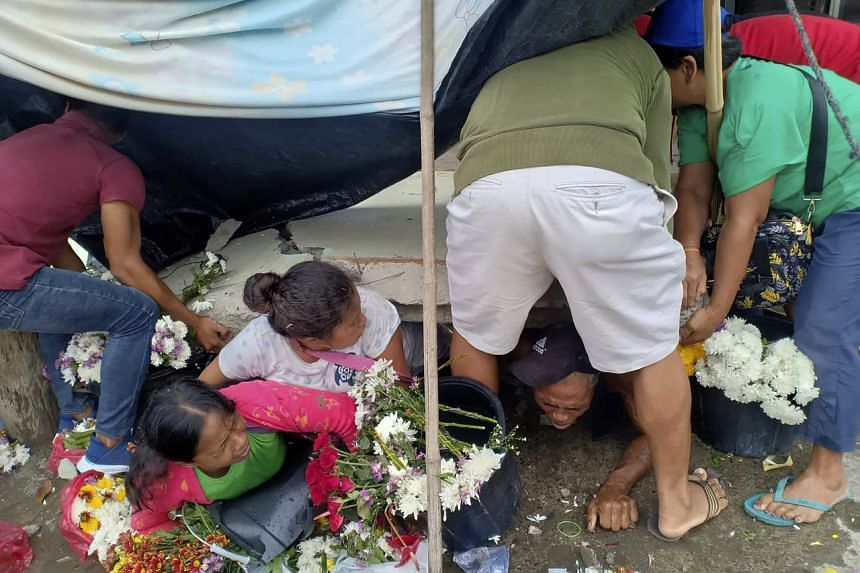 Trapped flower vendors are pulled out from a collapsed wall following an earthquake that struck Padada, in the Philippines' Davao del Sur province, on Dec 15, 2019.
