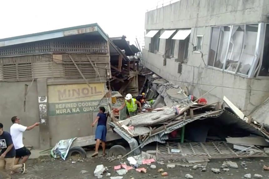 Rescue crew members look for trapped victims at a collapsed building in Padada, in the Philippines' Davao del Sur province, following an earthquake on Dec 15, 2019.