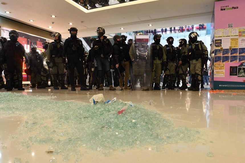 Police stand guard during a protest at the New Town Plaza shopping mall in Hong Kong's Sha Tin district on Dec 15, 2019.