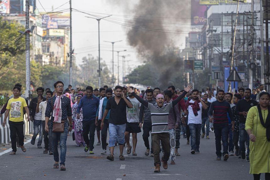 Smoke emits from burning tires as protestors defy a curfew in Gauhati, India, on Dec 12, 2019.