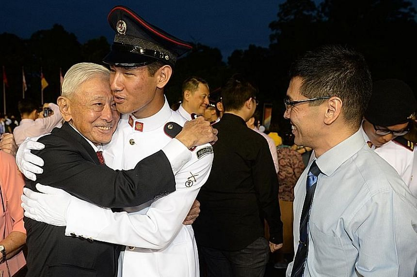 Former chief of defence force Winston Choo hugging grandson Daniel Choo at the commissioning parade yesterday, while son Warren Choo looks on. PHOTO: LIANHE ZAOBAO