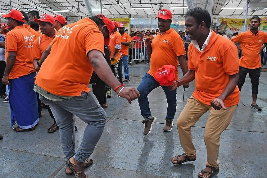 Migrant workers breaking into a dance routine upon hearing some of their favourite songs played over the loudspeakers at a ceremony to mark International Migrants Day - which falls on Wednesday - in Little India yesterday. About 5,000 workers attende