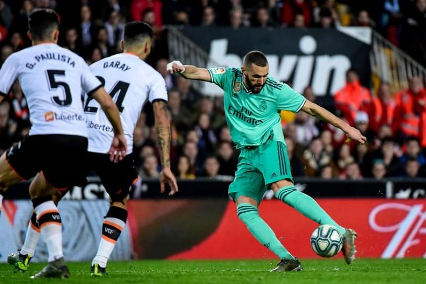 Real Madrid's Karim Benzema (right) vies with Valencia's Ezequiel Garay and Gabriel Paulista during their La Liga football match in Valencia on Dec 15, 2019.