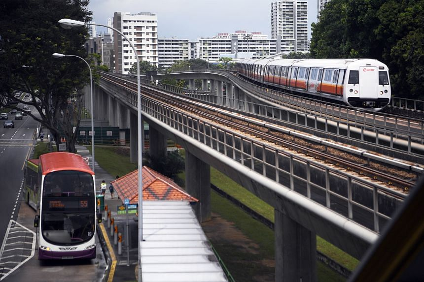 An SMRT train is seen heading to Bishan MRT Station as an SBS Transit double-decker bus leaves a bus stop.