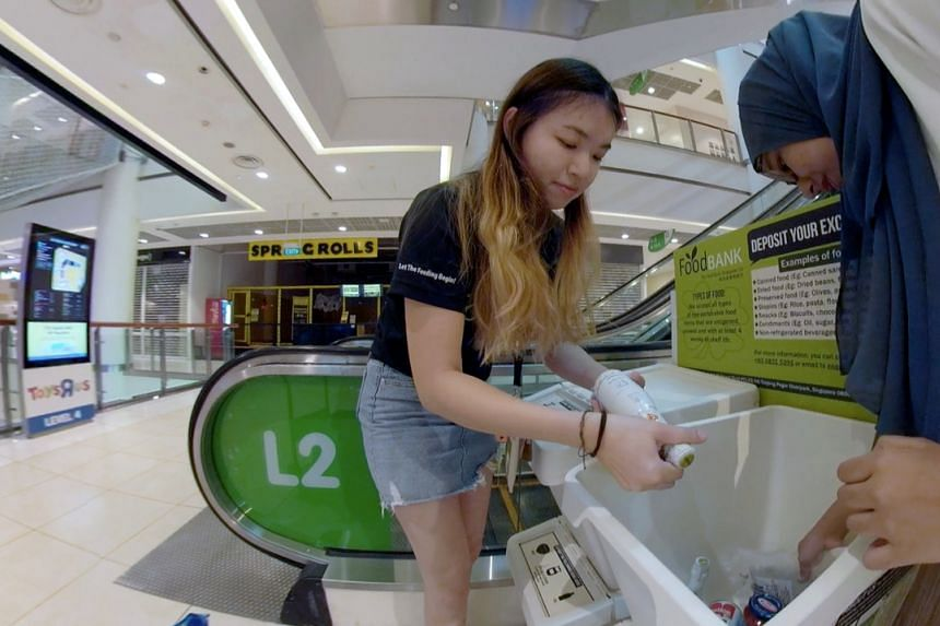 Ms Jessie Tan, a senior management associate with The Food Bank Singapore, picks up items from food donation boxes in City Square Mall.