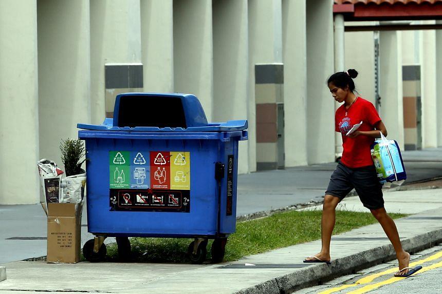 A woman walking past the recycling bin in Pasir Ris.