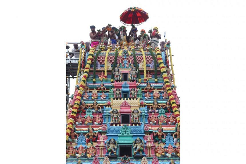 Hindu priests sprinkling sacred water from the roof over the rajagopuram, a five-tiered tower at the entrance of the Sri Layan Sithi Vinayagar Temple.