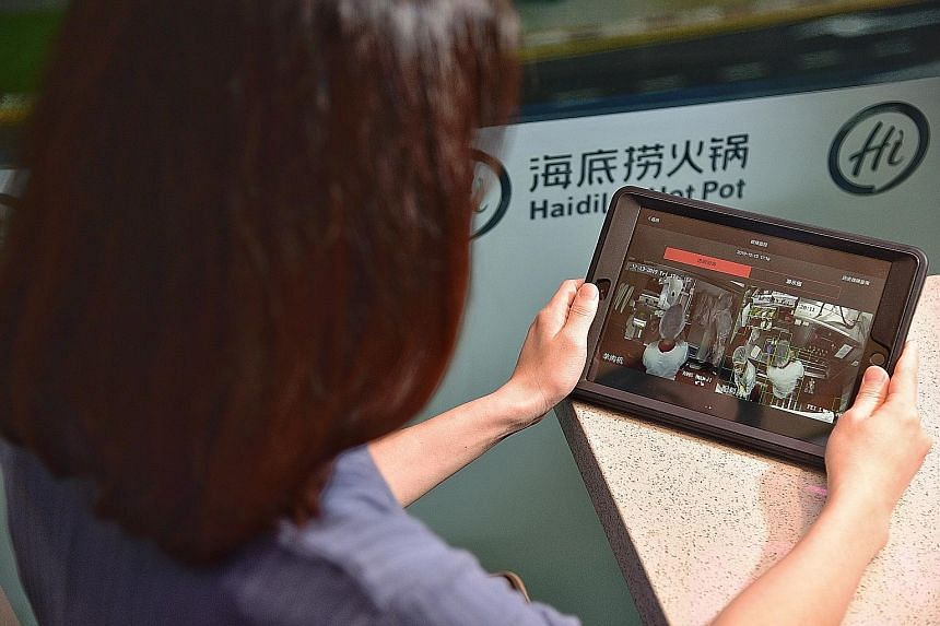 A customer watches the kitchen of Haidilao's PLQ mall outlet from a tablet that is used for ordering food. The restaurant chain hopes that the real-time videos will make diners feel assured that the food is safe to eat. A closed-circuit television ca