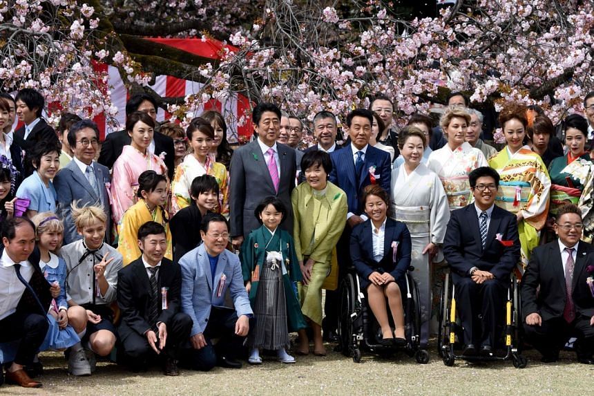In a photo taken on April 15, 2017, Japan's PM Shinzo Abe and his wife Akie pose with entertainers and athletes during the cherry blossom viewing party hosted by the prime minister in Tokyo.