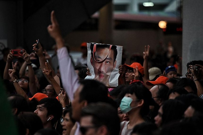 (Above) A protester at a Bangkok rally last Saturday holding a bag with a photo of Future Forward leader Thanathorn Juangroongruangkit. Thousands had gathered to show support for the party.
