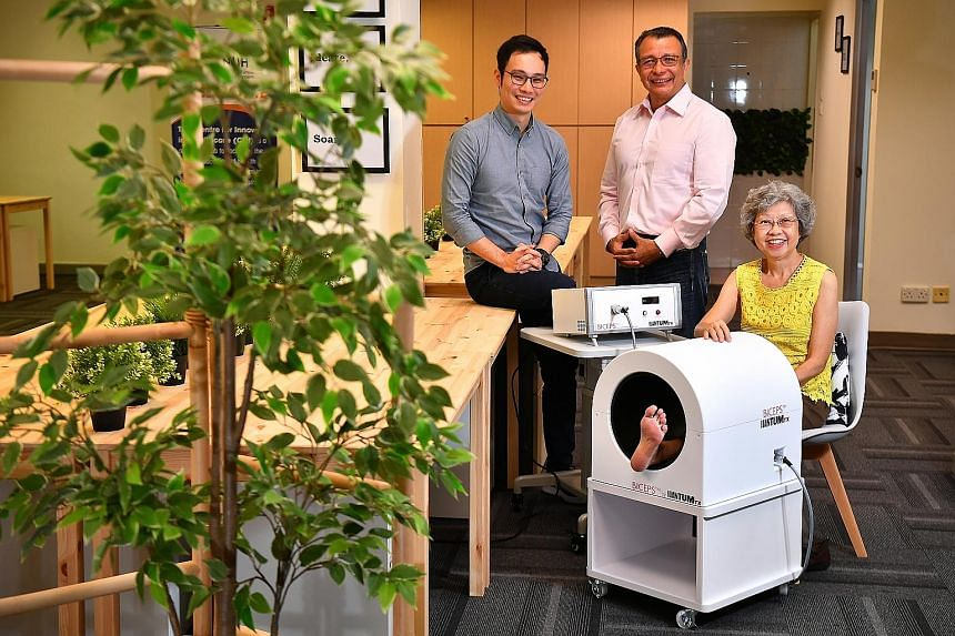 Retiree Maureen Swee on the Biceps machine at the Centre for Innovation in Healthcare co-working space, with QuantumTX CEO Ivan Goh (far left) and NUS Associate Professor Alfredo Franco-Obregon. Ms Swee, who used to lean on her umbrella while climbin