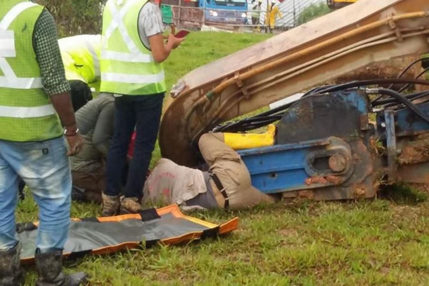 An excavator had toppled during a lifting operation and landed near a man, pinning his left leg on the ground.
