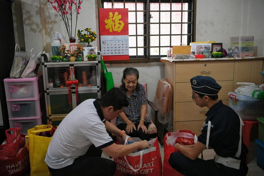Boys' Brigade member Matthew Ong (right) from Fairfield Methodist School delivers a food hamper to beneficiary Khoong Yoon Chun (centre) with the chairman of the Boys' Brigade charity drive Henry Tan in Redhill on Dec 18, 2019.