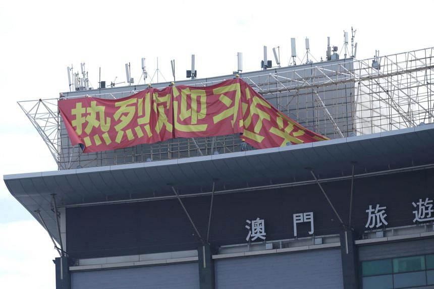 Workers hang up a giant banner on the roof of a building next to Macau Tower, welcoming Chinese President Xi Jinping to Macau on Dec 17, 2019.