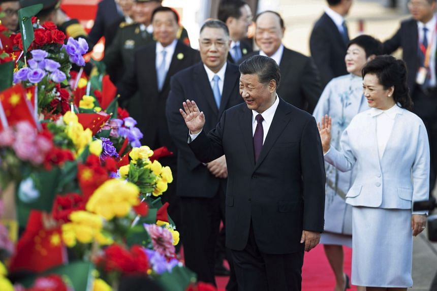 Chinese President Xi Jinping and his wife Peng Liyuan wave after arriving at Macao Airport.