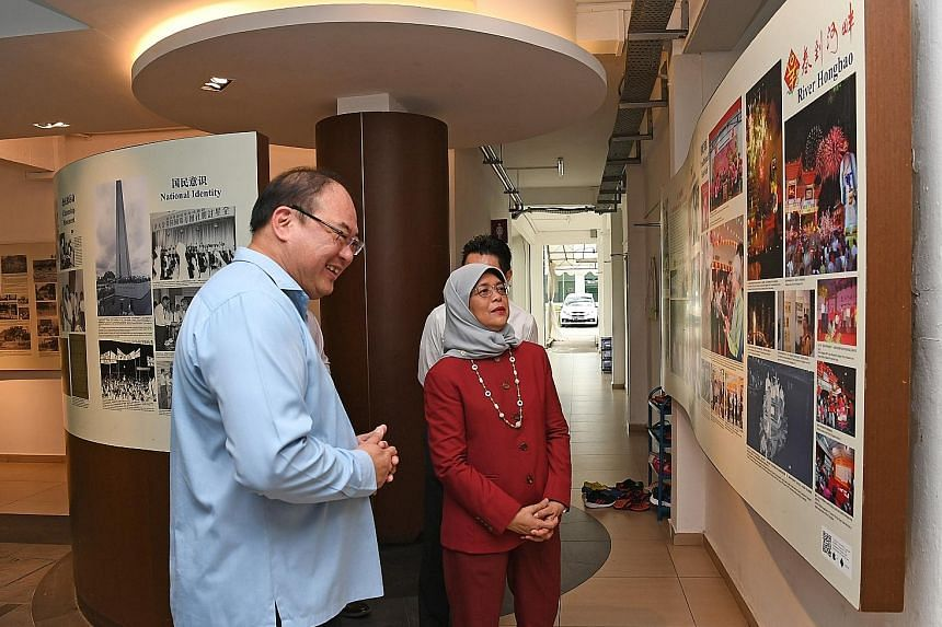President Halimah Yacob viewing the Singapore Federation of Chinese Clan Associations' heritage gallery with SFCCA president Tan Aik Hock yesterday. During her visit, Madam Halimah highlighted the importance of attracting young people to engage in an