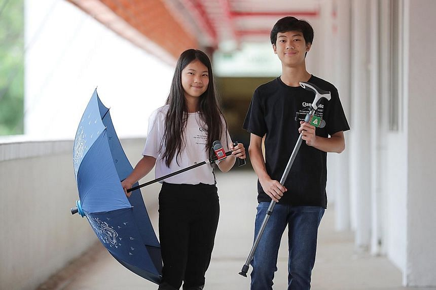 From left: Seng Ing Le, 13, and Seng Ian Hao, 15, with the QaneBrella - a two-in-one walking cane cum umbrella - and a walking stick fitted with the Qanemate, a clip that secures the walking aid to a railing or table to prevent it from falling over.