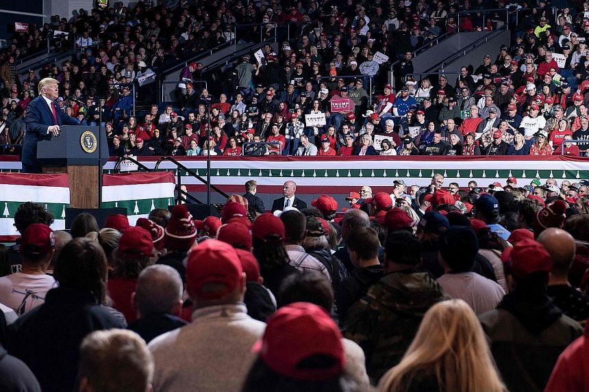 US President Donald Trump speaking at a campaign rally in Battle Creek, Michigan, on Wednesday, which took place as the House of Representatives voted to impeach him. Mr Mark Kampf from Pahrump, Nevada, joining other Trump supporters outside the Capi