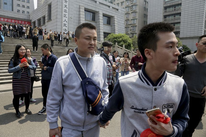 In a photo taken on April 13, 2016, Sun Wenlin (right) and his partner Hu Mingliang leave the court after a judge ruled against them in China's first gay marriage case in Changsha, Hunan.