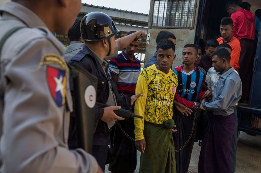 In a photo from Dec 11, 2019,  Rohingya detainees step out of a police van upon arriving at the court in the western Myanmar city of Pathein ahead of a hearing.