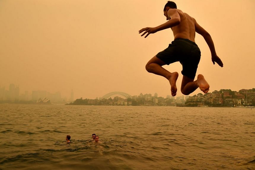 People taking to the water to cool off yesterday as haze blanketed Sydney. The city's air pollution levels ranged from poor to hazardous.