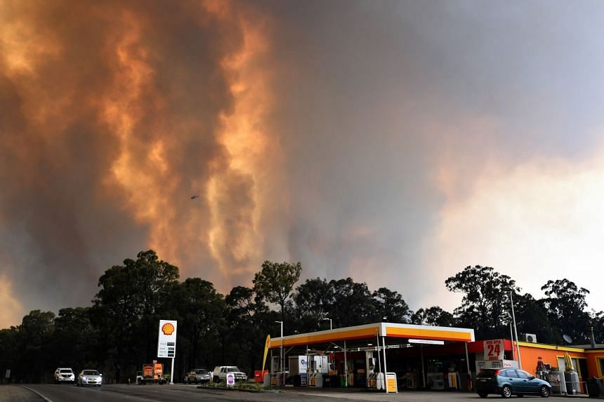 Smoke billowing from a bush fire near the town of Tahmoor in New South Wales yesterday. Around 2,000 firefighters were battling wildfires across the state.