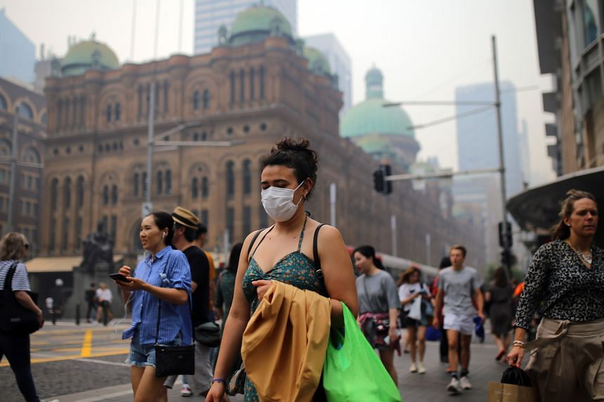 A pedestrian wears a mask as smoke and haze from bushfires in New South Wales blankets the CBD in Sydney on Dec 10, 2019.