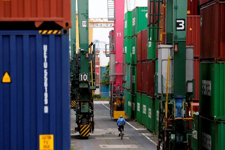 A cyclist riding past containers at an industrial port in Tokyo, Japan, on May 22, 2019.