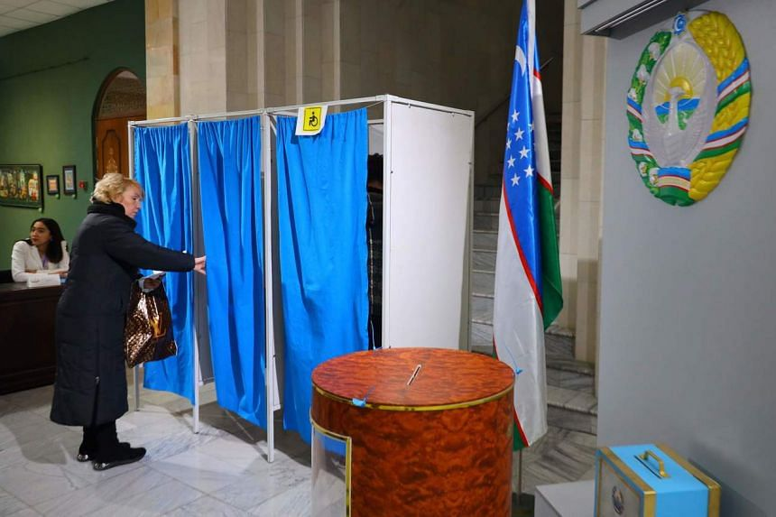 A woman goes in a polling booth before voting at a polling station in Tashkent, Uzbekistan on Dec 22, 2019.