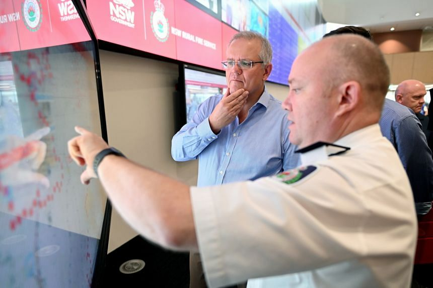Australian PM Scott Morrison (centre) is briefed by NSW RFS Commissioner Shane Fitzsimmons in the NSW Rural Fire Service control room in Sydney, Australia, on Dec 22, 2019.