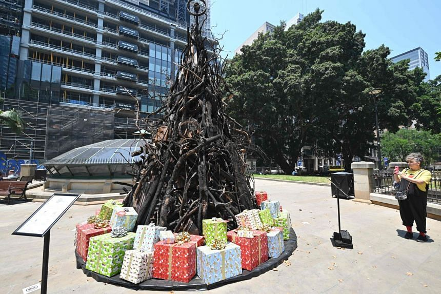 A woman takes a photo of an installation dubbed The Burnt Christmas Tree to support the Australian Red Cross' Disaster Relief and Recovery Fund in Sydney, on Dec 18, 2019.