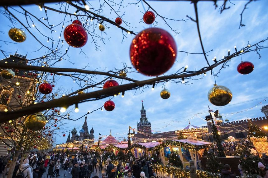 People walk in Red Square decorated for Christmas and New Year in Moscow, Russia, on Dec 21, 2019. For two weeks, temperatures in Moscow have topped 4 deg C, compared to the normal average for December of around minus 6 deg C.
