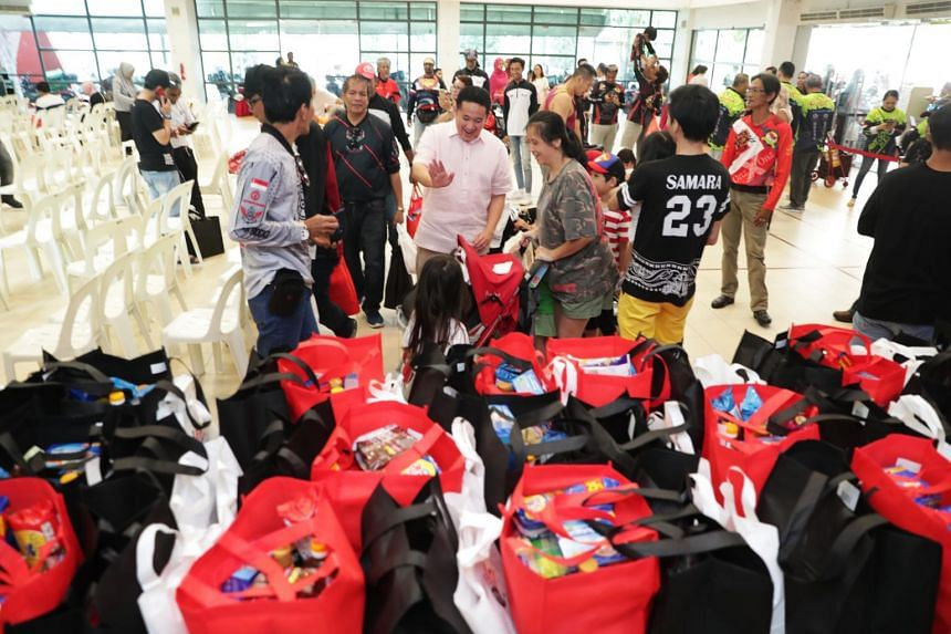 Senior Parliamentary Secretary for Home Affairs and Health Amrin Amin (centre) helped to distribute food bags to low-income families on Dec 22, 2019.