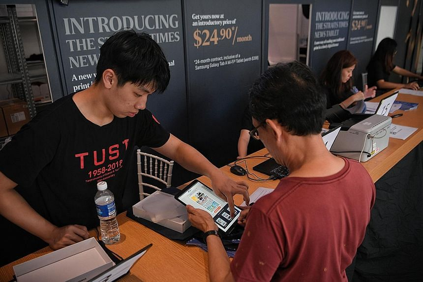 A subscriber collecting his Samsung Tab A 10.1-inch Wi-Fi tablet pre-loaded with the ST app at Plaza Singapura yesterday. Adjustments to the queue system have shortened the waiting time for subscribers collecting their tablets to about 10 to 15 minut