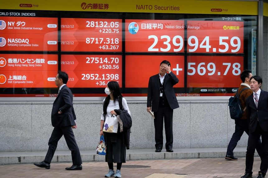 Pedestrians walk in front of an electric quotation board displaying the numbers on the Nikkei 225 Index on the Tokyo Stock Exchange, on Dec 13, 2019.