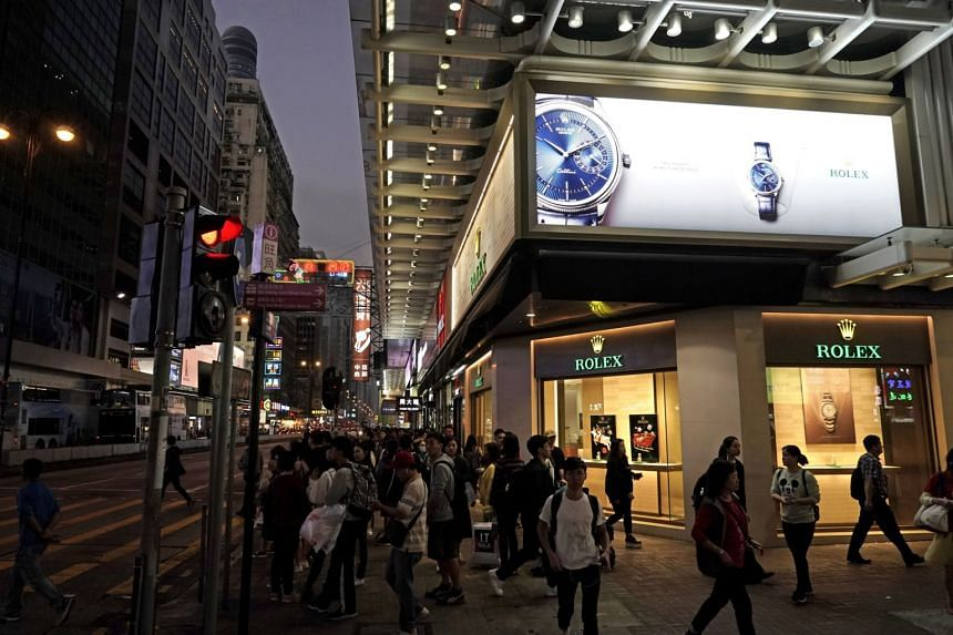 People walk past a luxury watch shop on a main street in Mongkok, a shopping district of Hong Kong.