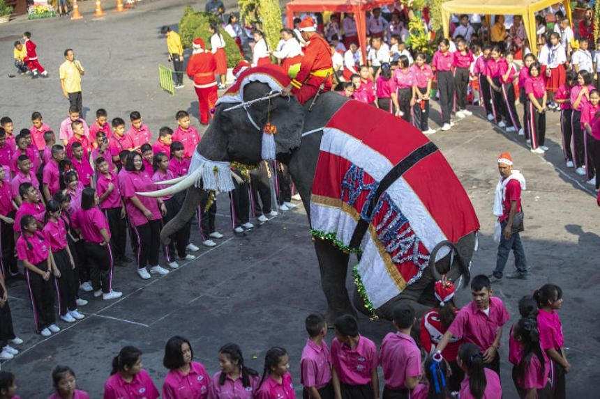 An elephant dressed in a Santa Claus costume performs in front of students at Jirasartwitthaya school during Christmas celebrations in Thailand on Dec 23, 2019.