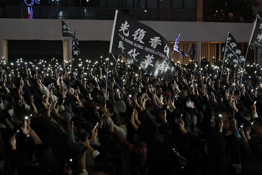 Protesters shining lights from cellphones and raising their hands to symbolise the pro-democracy movement's five demands at a rally in Hong Kong yesterday. PHOTO: ASSOCIATED PRESS