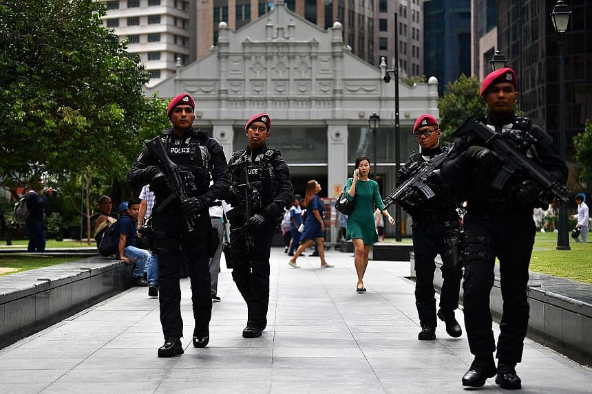 Officers from the Police Tactical Unit of the Special Operations Command on patrol in Raffles Place yesterday. They are among the specialist police units on patrol in the city area as Singapore prepares to ring in the new year.