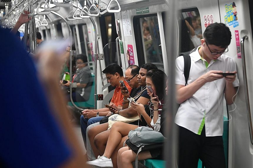 Top: MRT commuters using smartphones. Next year, Singapore will issue licences for up to four 5G networks instead of the original two, as it takes bolder steps to embrace a technology seen as crucial to its economic growth.