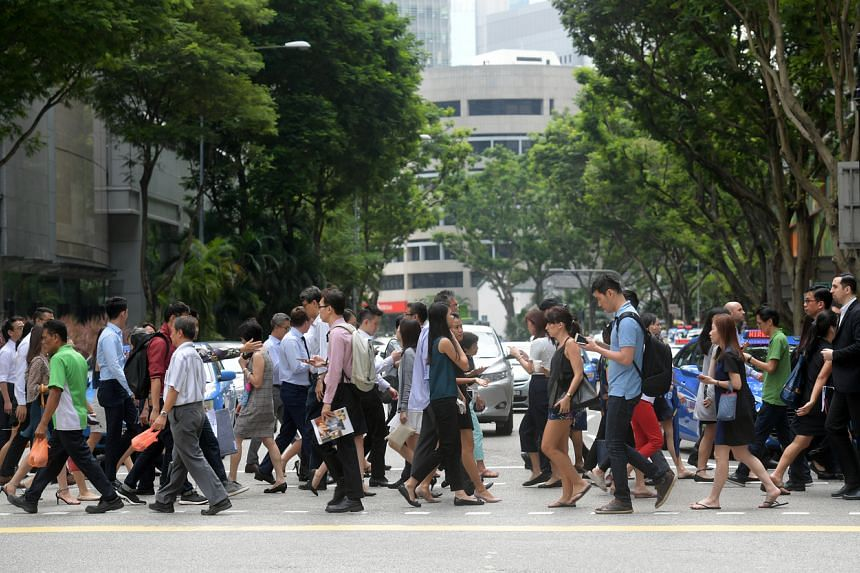 People cross a road in Singapore's central business district on June 29, 201