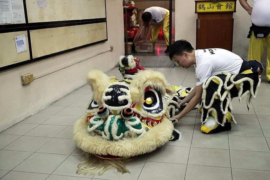 Above: Performer Ho Chin Wah, a civil servant, displaying Singapore's oldest lion head at the association's shophouse premises. The lion head weighs 15kg, compared with modern versions, which weigh only about 1kg. Left: After facing a youth membershi