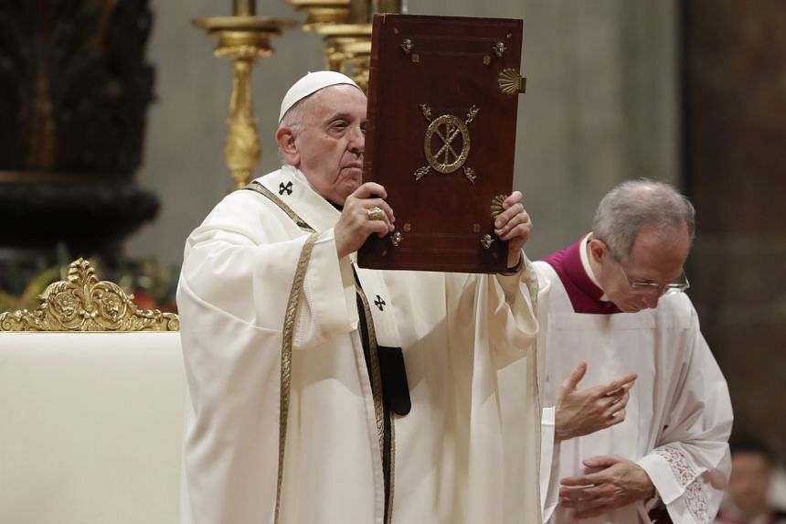Pope Francis holds up the book of Gospels as he celebrates Christmas Eve Mass in St. Peter's Basilica at the Vatican, Tuesday, on Dec 24, 2019.