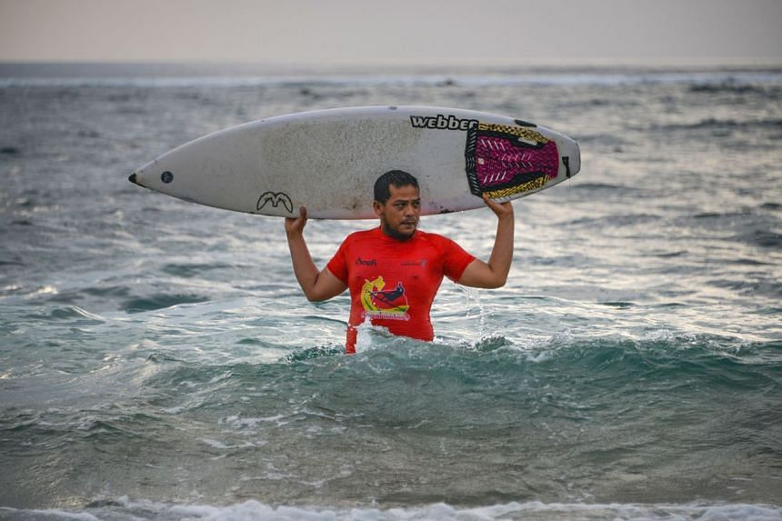 Mr Dery Setyawan, a survivor of the 2004 tsunami, holding his surfboard after surfing on Lhoknga beach in Banda Aceh, Aceh province.