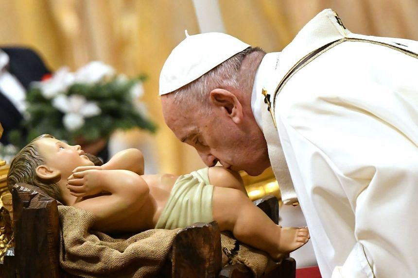 Pope Francis kisses a figurine of baby Jesus during a mass on Dec 24, 2019, at St Peter's basilica in the Vatican.
