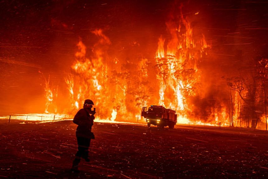 A firefighter records video on his phone of a wall of flames in Orangeville, Australia, on Dec 5, 2019.