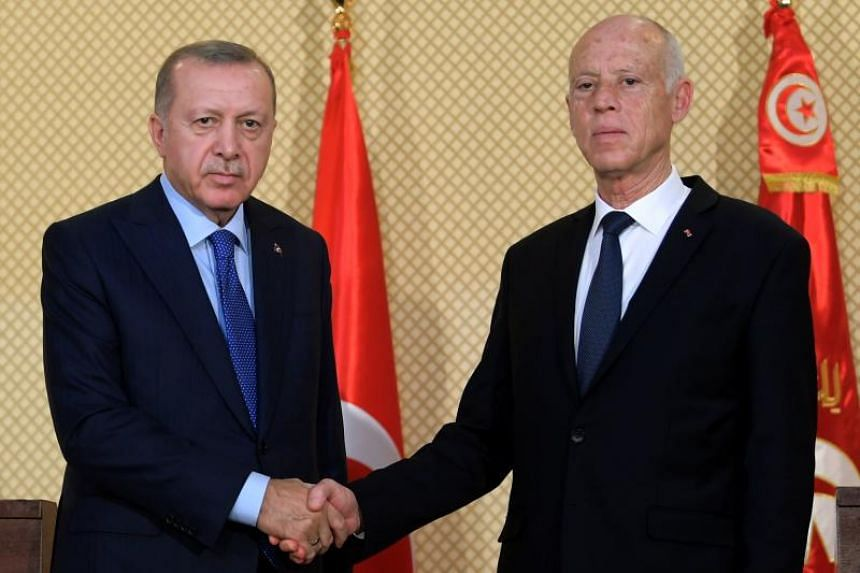 Turkish President Recep Tayyip Erdogan (left) shakes hands with Tunisian President Kais Saied during a welcoming ceremony in Tunis, on Dec 25, 2019.